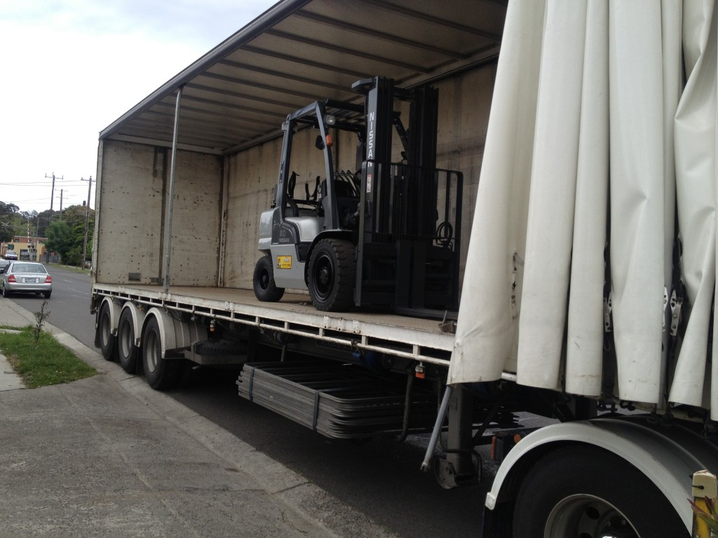 nissan forklift being loaded onto truck